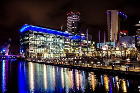 Modern illuminated business offices at night. Long reflections on the river from the lit windows and street lights. Tranquil water reflecting lights on its surface. Stock Photo