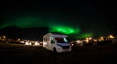 Picture shows a camping van under northern lights in Norway Stock Photo
