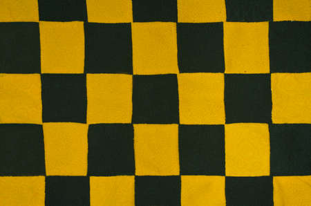 Texture with a chessboard pattern. Background is made of sewn pieces of yellow fabric and black fabric
