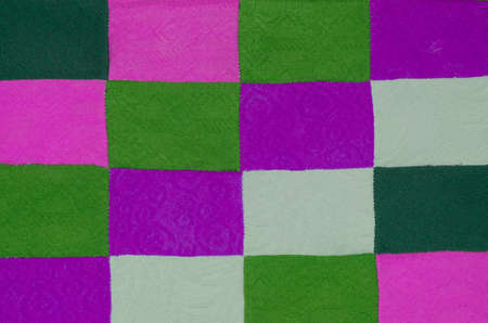 Amazing texture with a square pattern. Background is made of sewn pieces of purple,green and milky fabric