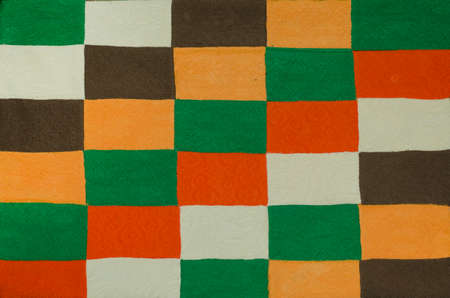 Texture with a colorful rectangular pattern. Background is made of sewn pieces of yellow,green,brown,orange and milky fabric