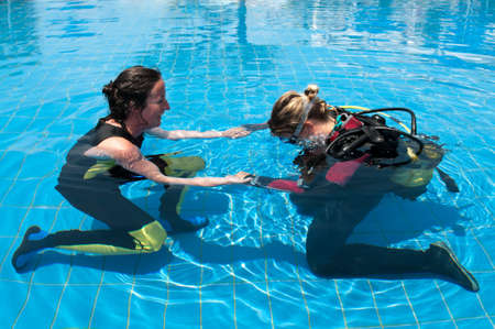 woman diving: Scuba diving instructor and student in a swimming pool