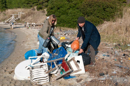 Clearing up rubbish washed up onto a small beach Stock Photo - 11305862