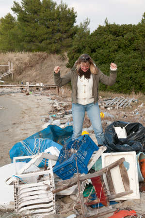 Upset woman looking at a pile for rubbish on a beach photo