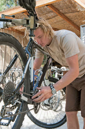 maintaining: Handsome young man maintaining a bicycle Stock Photo
