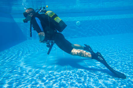 Young male learning to Scuba Dive in a Swimming Pool