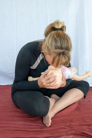 Practising CPR on an infant using a mannequin
