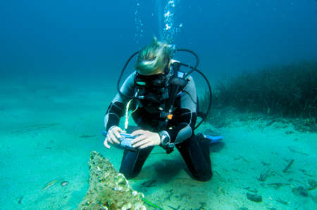 Underwater image of a female scuba diver taking pictures underwater