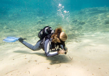 Underwater image of a female scuba diver hovering near the sand on a dive