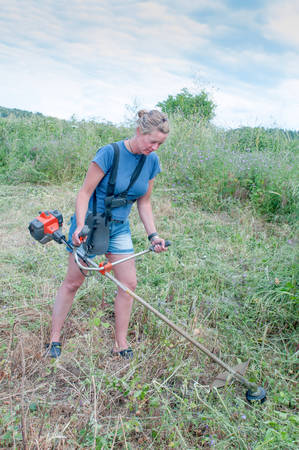 weeds: Woman clearing weeds with a strimmer