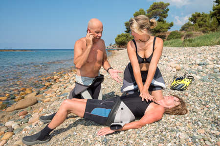 compressions: CPR training on a scuba diver on a beach