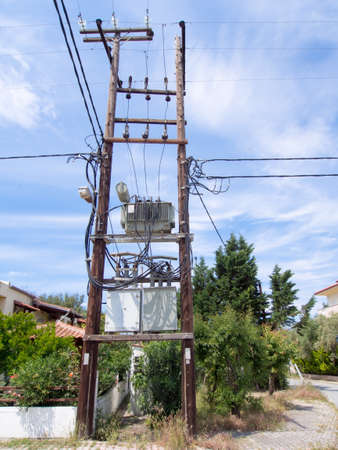 sub station: Electricity sub station on wooden poles in a village