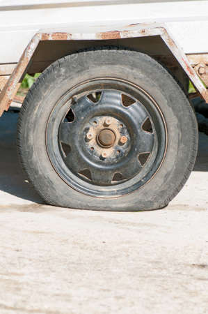flat tyre: An old wheel with a flat tyre