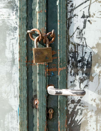 white washed: Old padlocked door with white washed glass