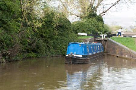 navigating: Narrow boat navigating a lock on a canal Stock Photo