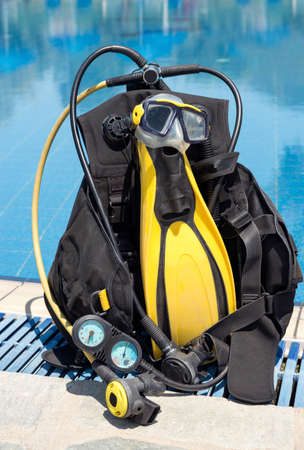 A set of Scuba gear set up by the side of a swimming pool