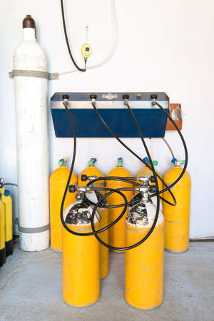 compressed air hose: Scuba Tanks being filled at a Filling Station