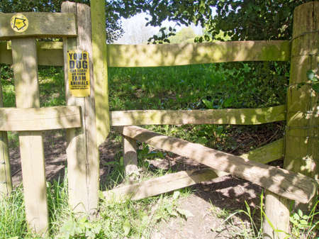 stile: Wooden stile and warning sign about dogs