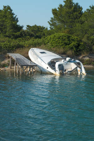 beached: Speedboat beached and part sunk at its mooring Stock Photo