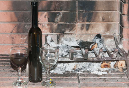 unloved: Wineglasses one full and one empty by a dead cold fire Stock Photo
