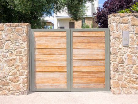 Solid wooden gates protecting a house.