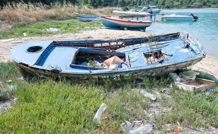 Old wooden boat falling to pieces filled with rubbish photo