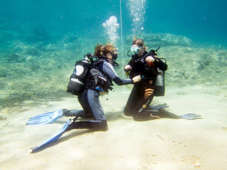 HALKIDIKI,GREECE-JULY 09 2014 : Two female scuba divers practise their skills underwater before a dive.Scuba diving is a sport carried out in many places around the world