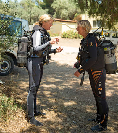 padi: PALIOURI,GREECE -  JULY 09 2014 :Two female Scuba Divers have a safety brief before they go for a dive.Diving is an adventurous sport with dive sites in most countries around the world.
