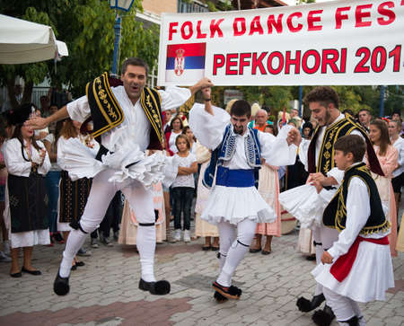 folk village: PEFKOHORI , GREECE - SEPTEMBER 19 2014 : Folk Dancers from several countries  taking part in the Annual Folk Dance festival in the village square of Pefkohori ,Greece,The Greek dancers perform their dance. Editorial