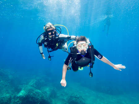 LOUTRA,GREECE-AUGUST 2014 :Female Scuba Diver taking part in a training dive with her Instructor.More women are taking up diving with dive schools around the world