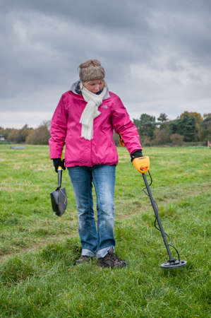 scavenge: WORCESTER,UK-NOVEMBER 21 2010 :Woman with a metal detector searching in a field for buried metal. Editorial