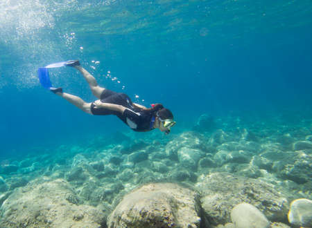 beneath: Loutra,Greece-August 24 2014 :A female snorkeler dives beneath the surface to explore underwater.Snorkeling is an easy sport for all ages to take part in