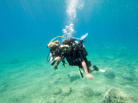 scuba diver: LOUTRA,GREECE-AUGUST 2014 :Female Scuba Diver taking part in a training dive with her Instructor.More women are taking up diving with dive schools around the world