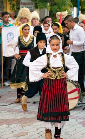 folk village: PEFKOHORI , GREECE - SEPTEMBER 19 2014 : Folk Dancers from several countries  taking part in the Annual Folk Dance festival in the village square of Pefkohori ,Greece