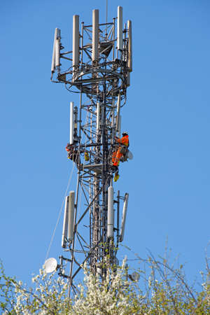 carry out: WORCESTER,UK - APRIL 14 2015 : Maintenance workers carry out repairs high up on a communications tower using saftey equipment