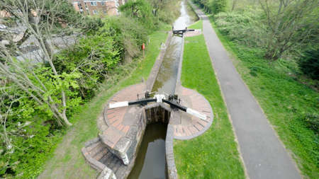 canal lock: Aerial image of a peaceful canal lock with a small towpath along side.