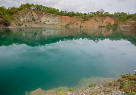 un used: An un used quarry filled with water surrounded by trees Stock Photo