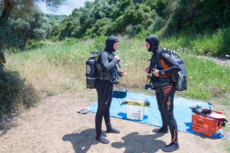 padi: AVLAKI,GREECE-JULY 04 2015 :Two female Scuba Divers have a safety brief before they go for a dive.Diving is an adventurous sport with dive sites in most countries around the world.
