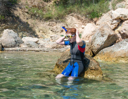 wetsuit: Female snorkeler wearing a wetsuit sat on a rock in shallow water adjusting her mask and snorkel ready to go snorkeling