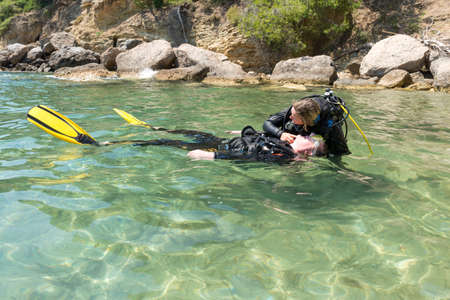 diving save: Diver checks casualty for breathing during a rescue practice Stock Photo