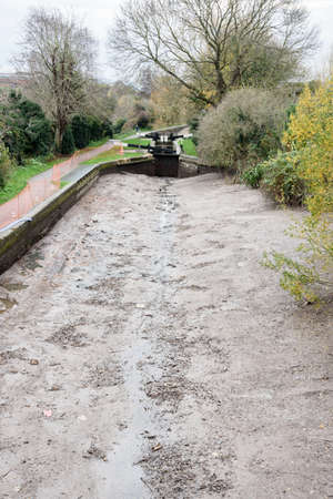 drained: A canal drained of water for repairs.Mud and rubbish covers the bottom of the canal