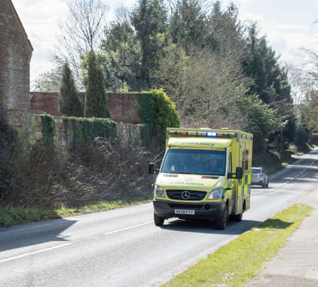 call out: Hawkhurst,Kent,UK - March 25 2016 : An Ambulance on an emergency call out races along a road with its sirens on and blue lights flashing Editorial