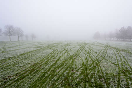Empty golf course fairway on a cold and misty day