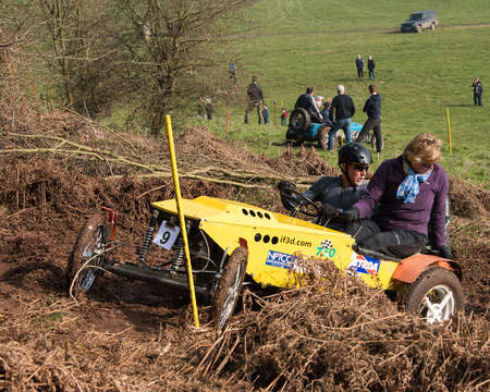furthest: Worcester , UK - March 13 2016 : Competitors take part in a hill climb to see who can drive their car furthest up a muddy hillside. Editorial