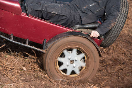 rear wheel: Close up view of the rear wheel of a car spinning trying to get up a muddy field Stock Photo