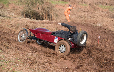 furthest: Worcester , UK - March 13 2016 : Competitors take part in a hill climb to see who can drive their car furthest up a muddy hillside. This was a free to enter event with no photography restrictions. Editorial