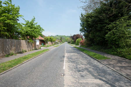grass verge: Quiet village road without any traffic