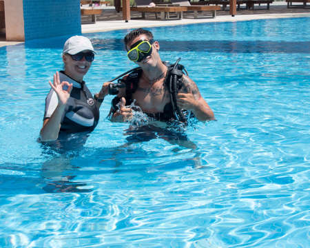 scuba woman: Paliouri,Greece - June 15 2016: Young  man tries a scuba dive in a pool with an instructor.Scuba diving is a fun sport enjoyed by many people. Editorial