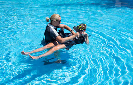 padi: Paliouri,Greece - June 15 2016: Young  woman tries a scuba dive in a pool with an instructor.Scuba diving is a fun sport enjoyed by many people.
