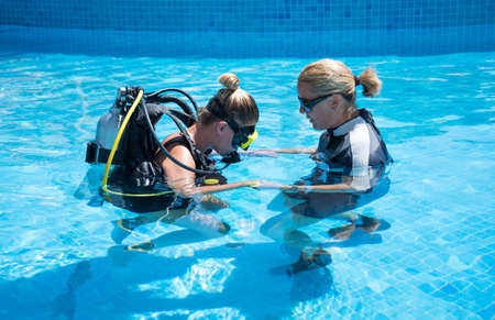 padi: Paliouri,Greece - June 15 2016:Young woman tries a scuba dive in a pool with an instructor.Scuba diving is a fun sport enjoyed by many people.